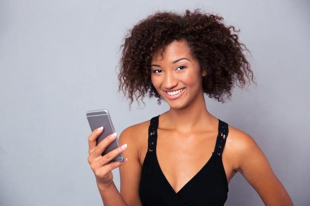 Portret uśmiechniętej kobiety afro american za pomocą smartfona na szarej ścianie