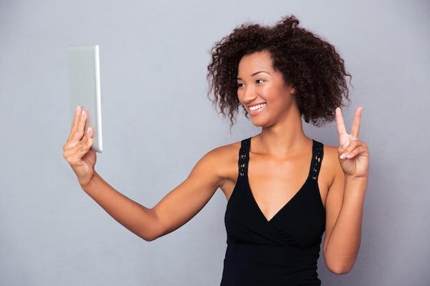 Portret uśmiechniętej kobiety afro amerykanki podejmowania rozmowy wideo na komputerze typu tablet na szarej ścianie