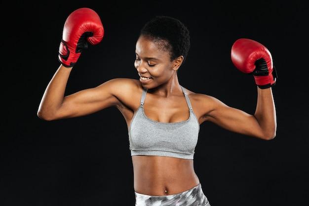 Portret uśmiechniętej kobiety fitness stojącej z rękawicami bokserskimi w pozie zwycięstwa odizolowanej na czarnej ścianie