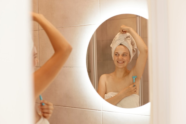 Portret uśmiechniętej kobiety golącej się pod pachami w łazience, trzymającej w ręku golarkę, patrzącej w lustro, owiniętej białym ręcznikiem, stojącej w łazience i wykonującej depilację.
