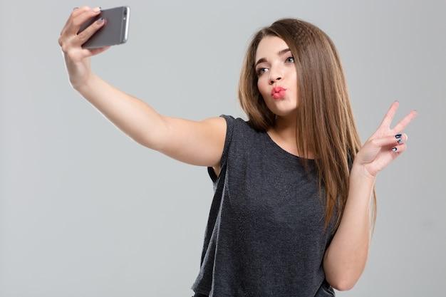 Portret uśmiechniętej kobiety, która robi zdjęcie selfie na smartfonie i pokazuje znak pokoju na białym tle