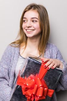 Portret uśmiechniętej kobiety ładnej otwierającej pudełko