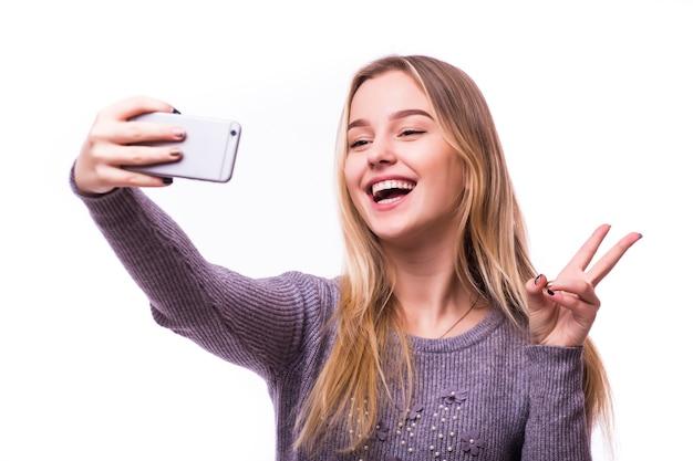 Portret uśmiechniętej kobiety ładny robienie selfie zdjęcie na smartfonie na białym tle na białej ścianie