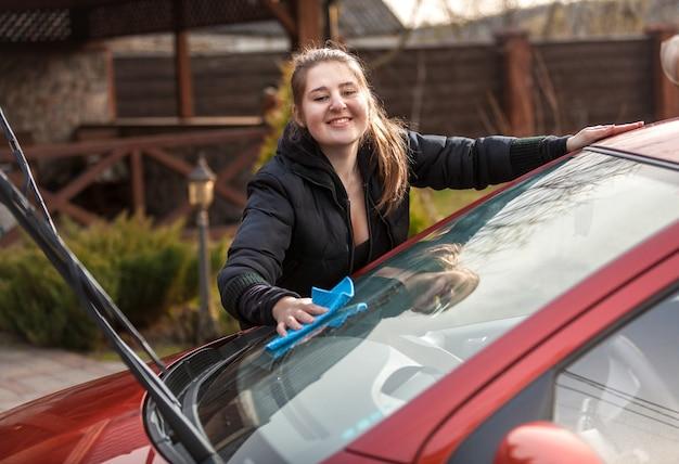 Portret uśmiechniętej kobiety myjącej przednią szybę samochodu na podwórku