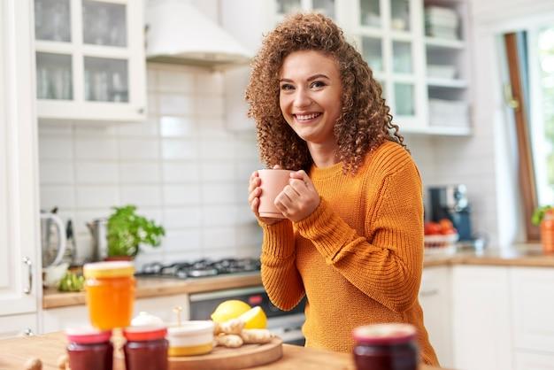 Portret uśmiechniętej kobiety pijącej herbatę w kuchni