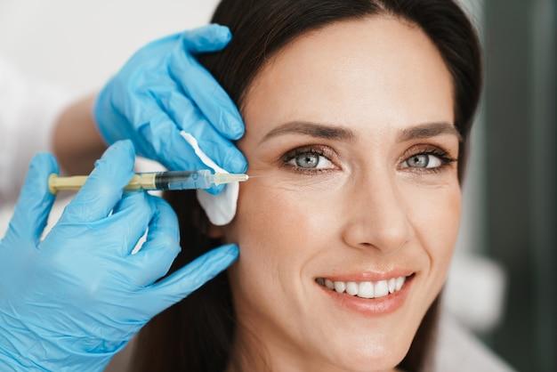 Portret uśmiechniętej kobiety poddawanej zabiegowi mezoterapii twarzy przez specjalistę w rękawiczkach w salonie kosmetycznym