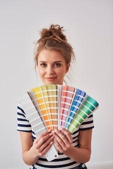 Portret uśmiechniętej kobiety pokazującej próbkę koloru