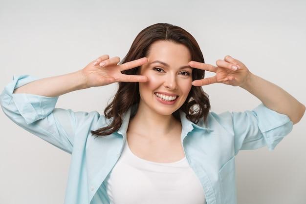 Portret uśmiechniętej kobiety pokazującej znak zwycięstwa i patrzącej w kamerę na białym tle
