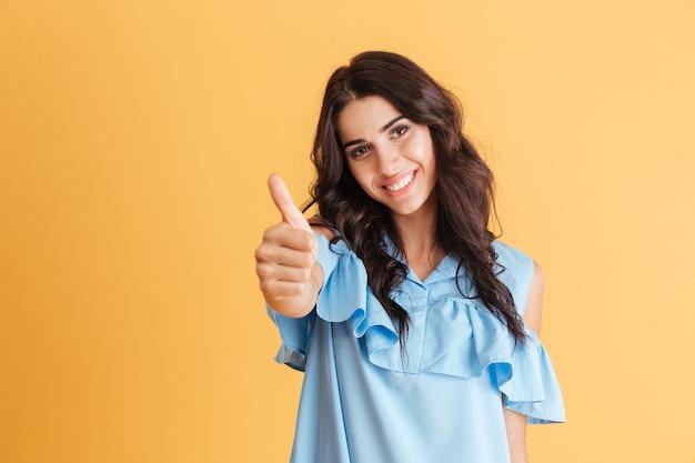 Portret uśmiechniętej kobiety pokazujący kciuk w górę