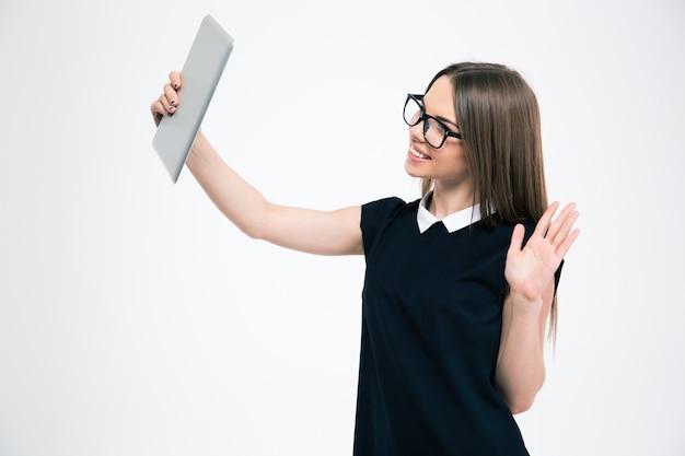 Portret uśmiechniętej kobiety prowadzącej czat wideo na komputerze typu tablet na białym tle