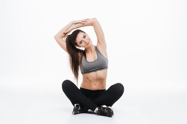 Portret uśmiechniętej kobiety sportowej rozciągającej ręce siedząc na podłodze na białym tle