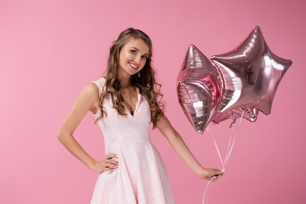 Portret uśmiechniętej kobiety trzymającej balony w kształcie gwiazdy