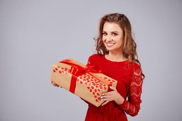Portret uśmiechniętej kobiety trzymającej prezent