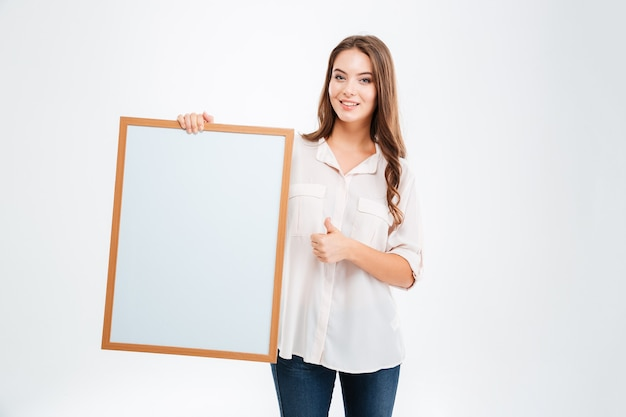Portret uśmiechniętej kobiety trzymającej pustą deskę i pokazującej kciuk na białym tle na białej ścianie