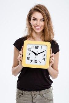Portret uśmiechniętej kobiety trzymającej zegar ścienny na białym tle