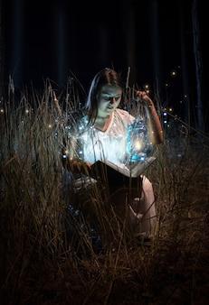 Portret uśmiechniętej kobiety w koszuli nocnej siedzącej przy polu w nocy i czytającej książkę