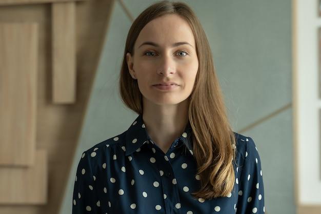 Portret uśmiechniętej kobiety w koszuli stojącej w nowoczesnym biurze