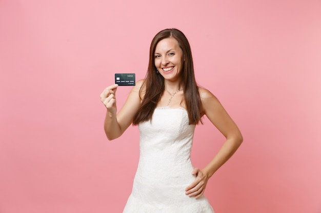 Portret uśmiechniętej kobiety w pięknej koronkowej białej sukni trzymającej kartę kredytową