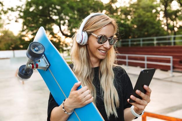 Portret uśmiechniętej kobiety w słuchawkach i okularach przeciwsłonecznych, piszącej na telefonie komórkowym, trzymając deskę w skateparku