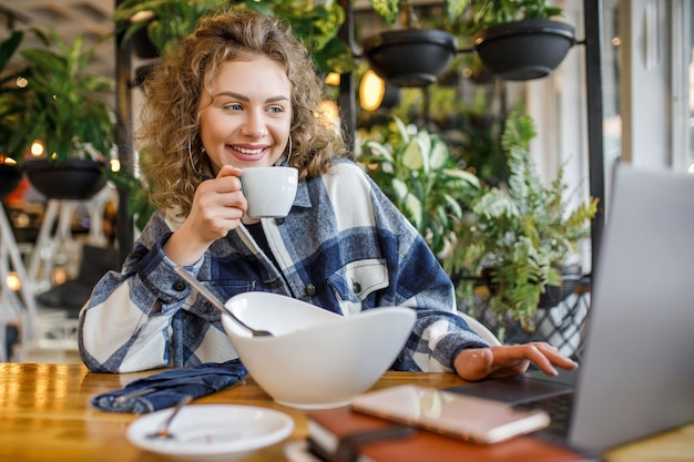 Portret uśmiechniętej kobiety w stroju casual z filiżanką kawy i sałatką podczas śniadania w kawiarni