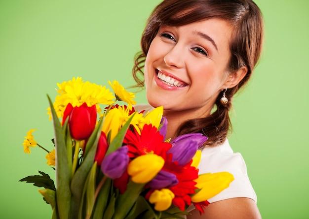 Portret uśmiechniętej kobiety z kolorowymi kwiatami