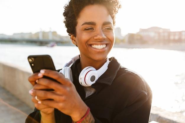 Portret uśmiechniętej kobiety z kręconą fryzurą afro trzymającą smartfona podczas spaceru wzdłuż brzegu rzeki