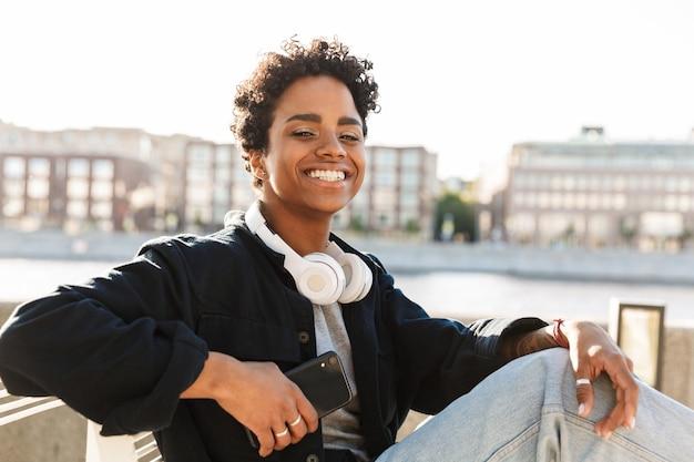 Portret uśmiechniętej kobiety z kręconą fryzurą afro, trzymającą smartfona, siedząc na ławce w pobliżu brzegu rzeki