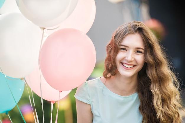 Portret uśmiechniętej kobiety z latającymi wielokolorowymi balonami w mieście