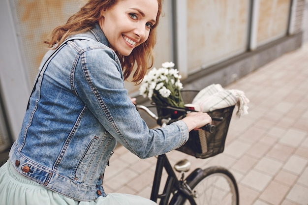Portret uśmiechniętej kobiety z rowerem