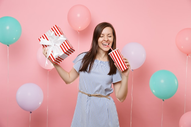 Portret uśmiechniętej kobiety z zamkniętymi oczami w niebieskiej sukience trzymającej czerwone pudełko z prezentem przedstawia sodę lub colę z plastikowego kubka na różowym tle z kolorowymi balonami. urodzinowe przyjęcie świąteczne.