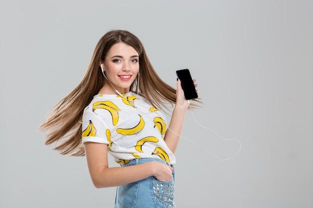 Portret uśmiechniętej kobiety ze słuchawkami pokazującymi pusty ekran smartfona na białym tle