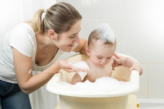 Portret uśmiechniętej matki bawiącej się z dzieckiem w wannie