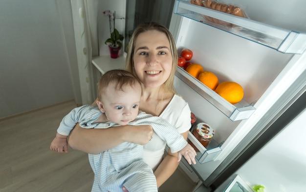 Portret uśmiechniętej matki pozującej z synkiem obok otwartej lodówki w nocy