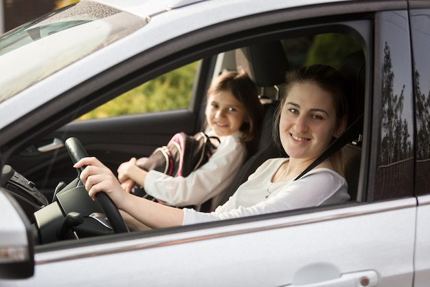 Portret uśmiechniętej matki zabierającej córkę do szkoły samochodem