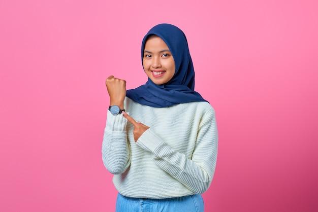 Portret uśmiechniętej młodej azjatki pokazującej i wskazującej zegarek palcem