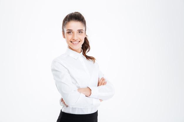 Portret uśmiechniętej młodej bizneswoman stojącej z założonymi rękami na białym tle na białej ścianie