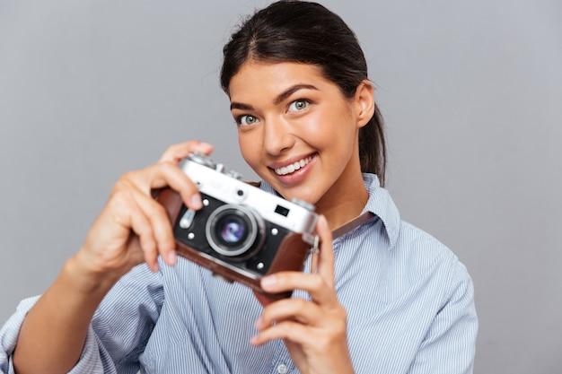 Portret uśmiechniętej młodej brunetki trzymającej zdjęcie z przodu izolowane na szarej ścianie