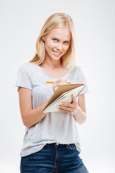Portret uśmiechniętej młodej dziewczyny robiącej notatki w notatniku na białej ścianie
