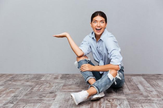 Portret uśmiechniętej młodej dziewczyny siedzącej na podłodze i trzymającej copyspace na dłoni odizolowanej na szarej ścianie