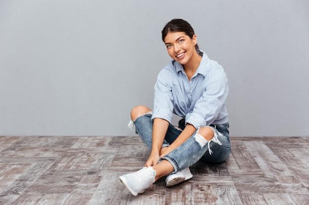 Portret uśmiechniętej młodej dziewczyny siedzącej na podłodze odizolowanej na szarej ścianie
