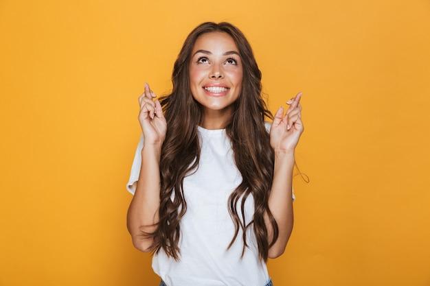 Portret uśmiechniętej młodej dziewczyny z długimi brunetkami stojącej na żółtej ścianie, trzymając kciuki za szczęście