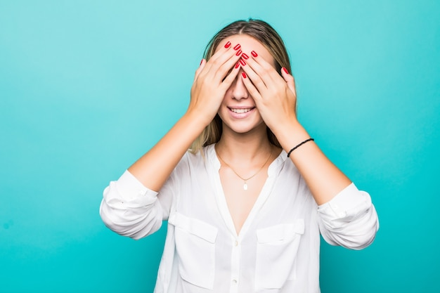 Portret uśmiechniętej młodej kobiety obejmujące oczy z rękami na białym tle nad niebieską ścianą