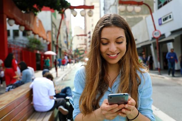Portret uśmiechniętej młodej kobiety spaceru w mieście sao paulo z telefonem komórkowym, brazylia