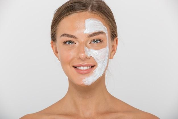 Portret uśmiechniętej młodej kobiety topless na białym tle, patrząc z pół twarzy pokrytej białą maską