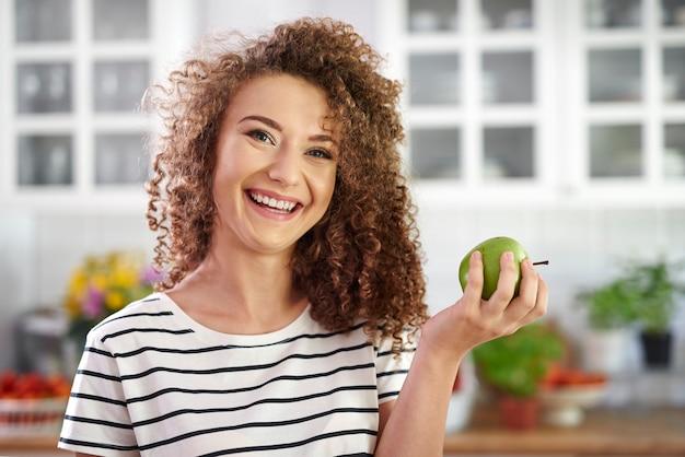Portret uśmiechniętej młodej kobiety trzymającej jabłko