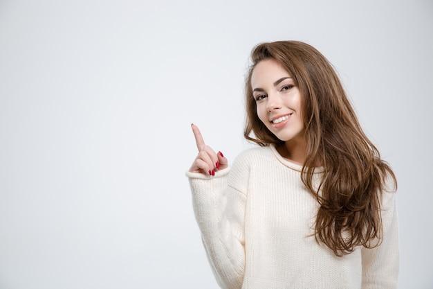 Portret uśmiechniętej młodej kobiety, wskazując palcem w górę na copyspace na białym tle
