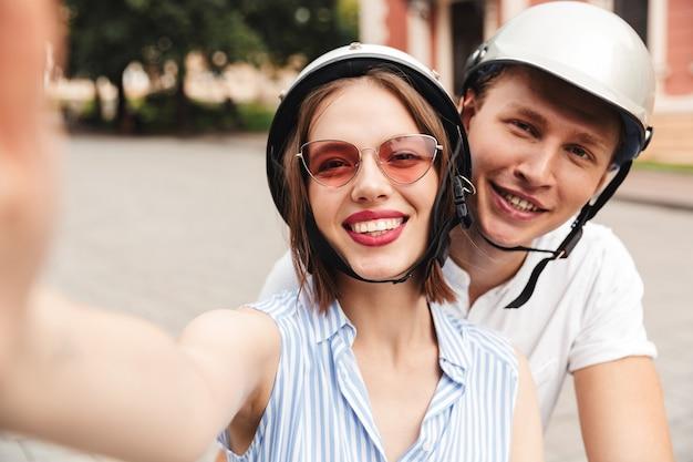 Portret uśmiechniętej młodej pary w kaskach, razem jeżdżącej na motocyklu na ulicy miasta, biorąc selfie