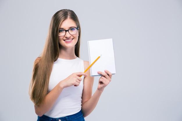 Portret uśmiechniętej nastolatka pokazującego pusty notatnik na białym tle