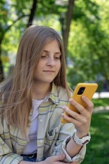 Portret uśmiechniętej nastolatki ze smartfonem w dłoniach czyta e-maile gra w gry