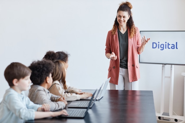 Portret uśmiechniętej nauczycielki rozmawiającej z grupą dzieci korzystających z komputerów podczas lekcji informatyki w szkole